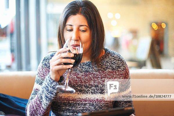 Reife Frau trinkt rot und liest digitales Tablett in der Weinstube