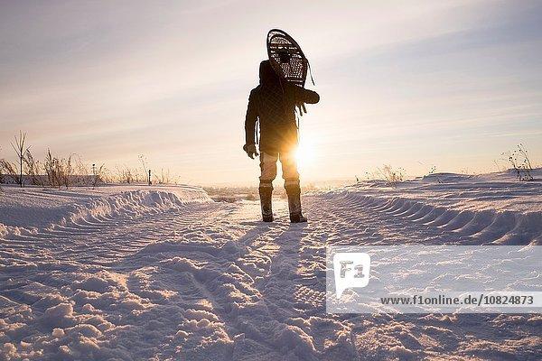 Rückansicht eines Mannes mit Schneeschuhen auf den Schultern in verschneiter Landschaft  Ural  Russland