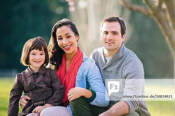 Portrait of young couple with daughter sitting on lap in park