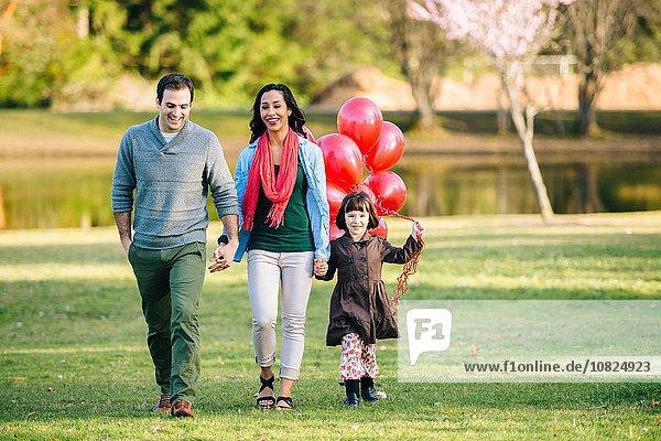Junges Paar und Tochter mit einem Haufen roter Luftballons beim Spaziergang im Park