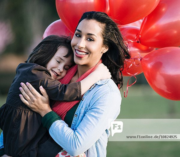 Portrait of girl with bunch of red balloons hugging mother in park