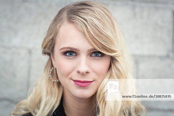 Junge blondhaarige Frau vor der Breeze-Blockwand mit Blick auf die Kamera lächelnd
