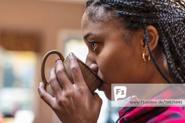 Nahaufnahme einer erwachsenen Frau in der Küche beim Kaffeetrinken