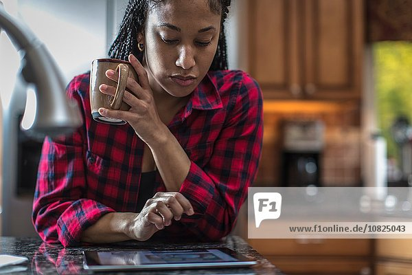 Mittlere erwachsene Frau am Küchenarbeitsplatz mit digitalem Tablett