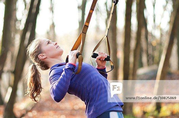 Seitenansicht einer jungen Frau  die sich mit Hilfe von Widerstandsbändern nach hinten beugt.