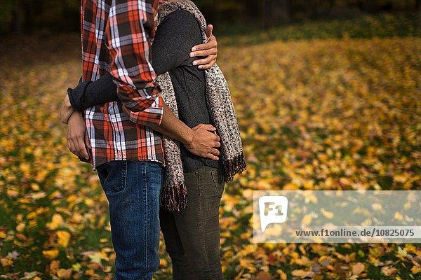 Ausschnitt eines mittleren erwachsenen Paares  das sich im Herbstwald umarmt.