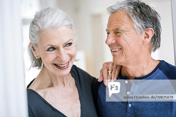 Senior woman with hand on senior mans shoulder smiling
