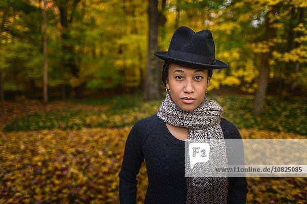 Porträt einer erwachsenen Frau mit Trilby und Schal im Herbstwald