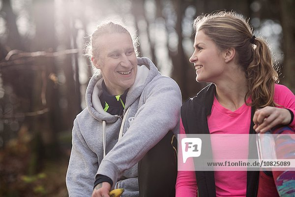 Couple wearing sports clothing holding water bottle sitting face to face smiling