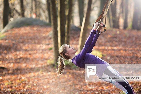 Seitenansicht einer jungen Frau im Wald  die sich mit Hilfe von Widerstandsbändern zurücklehnt und nach oben schaut.