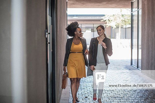 Two young businesswomen walking and talking outside office