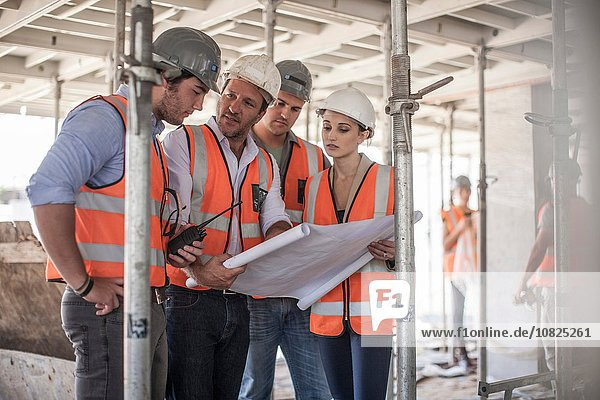 Vier Bauherren mit Bauplan auf der Baustelle