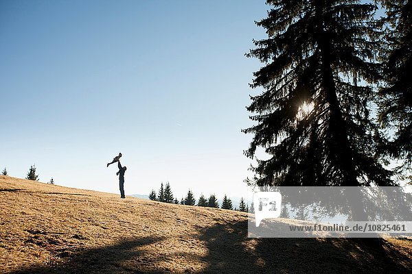 Silhouette of man holding up toddler daughter on hill  Tegernsee  Bavaria  Germany