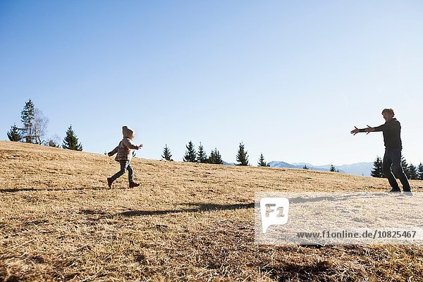 Female toddler running to father on hill  Tegernsee  Bavaria  Germany