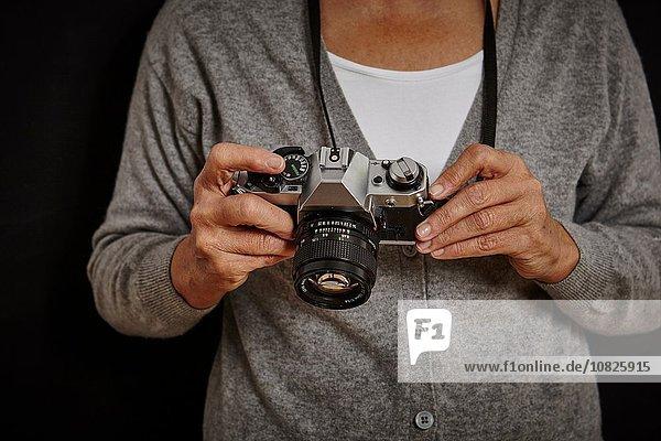 Mature woman holding camera