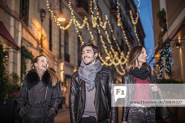 Niedriger Winkel Vorderansicht von Freunden  die abends lächelnd die Straße hinuntergehen.