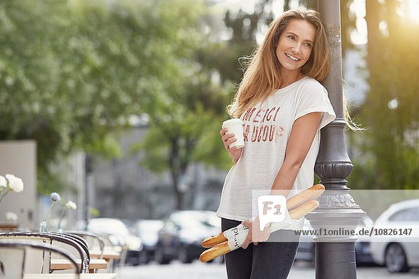 Young woman leaning against lamppost holding baguettes and disposable cup looking away smiling