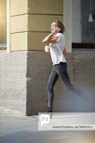 Seitenansicht einer jungen Frau  die mit dem Smartphone auf der Straße telefoniert.