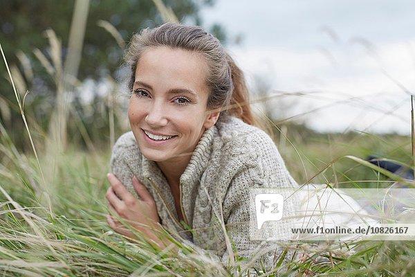 Junge Frau vorne auf Gras liegend mit lächelndem Blick auf die Kamera