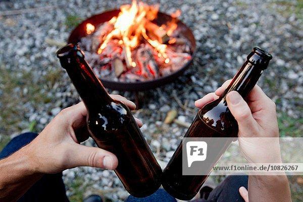 Hände halten Bierflaschen mit Lagerfeuer