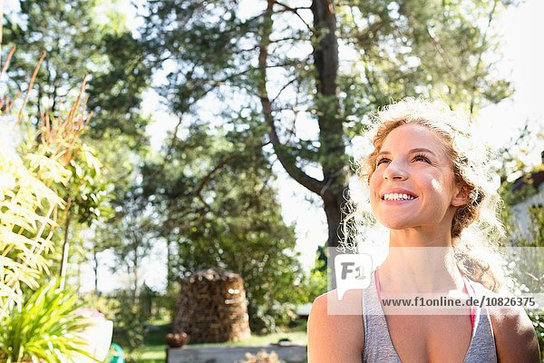 Young woman looking up smiling in sunlight  portrait