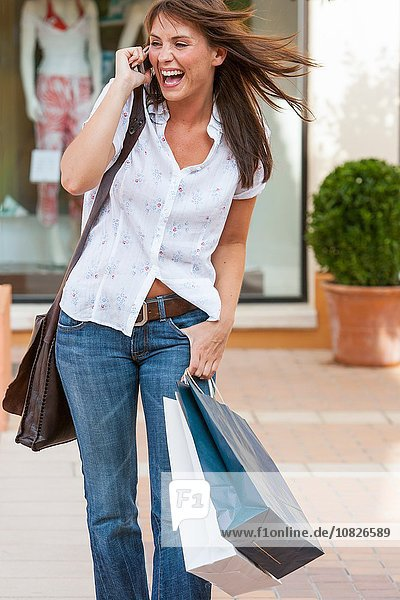 Young female shopping carrying shopping bags and chatting on mobile phone  Majorca  Spain