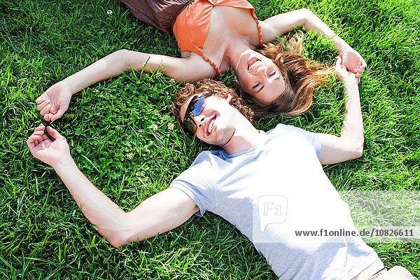 Draufsicht auf ein romantisches junges Paar  das auf einer Gartenwiese liegt.