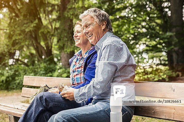 Happy adult couple eating sandwich on park bench
