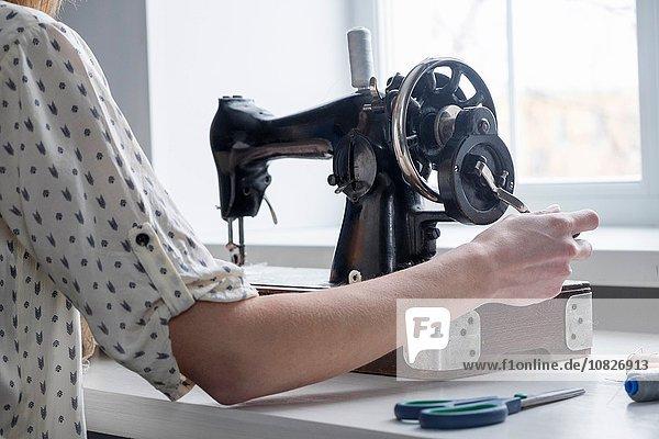Beschnittene Ansicht der Frau mit der Vintage-Nähmaschine