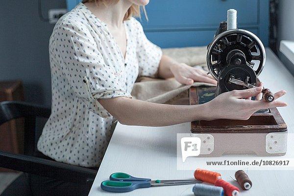 Ausschnitt einer Frau beim Nähen auf einer Vintage-Nähmaschine