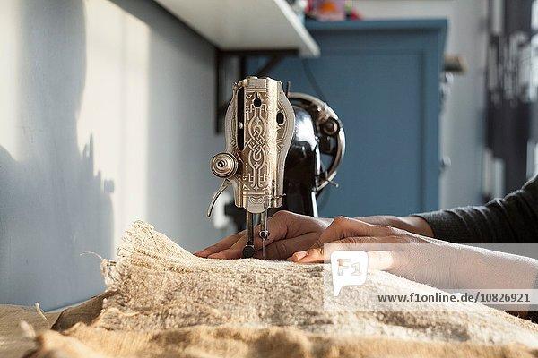 Nahaufnahme von Frauenhänden beim Nähen von Textilien auf der Vintage-Nähmaschine