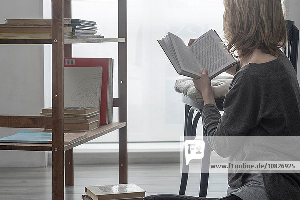 Frau sitzt auf dem Wohnzimmerboden und liest ein Buch.