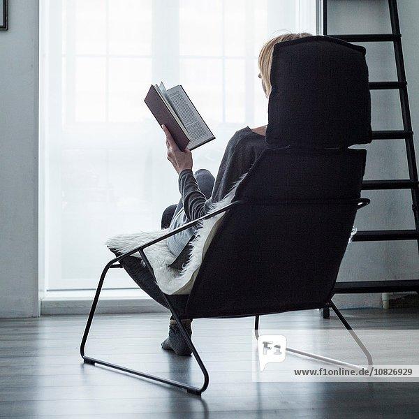 Frau sitzt auf einem Stuhl vor dem Fenster und liest ein Buch.
