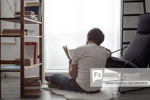 Mann sitzt auf dem Wohnzimmerboden und liest ein Buch.