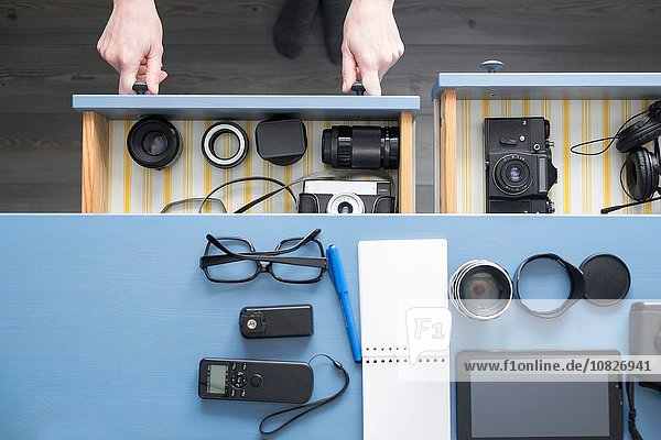 Overhead-Ansicht von Fotografinnen Hände öffnen Schreibtischschublade im Studio
