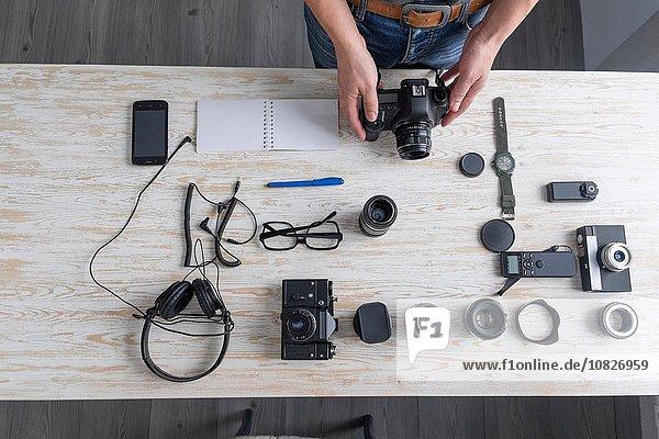 Overhead view of male photographer preparing camera on studio desk