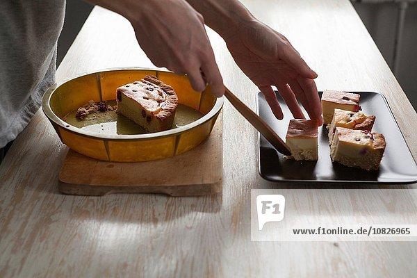 Weibliche Hände beim Auflegen des Kuchens auf die Schüssel an der Küchenzeile