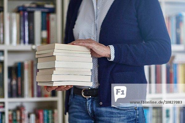 Abgeschnittene Aufnahme einer Frau  die einen Stapel Bücher aus dem Bücherregal trägt.