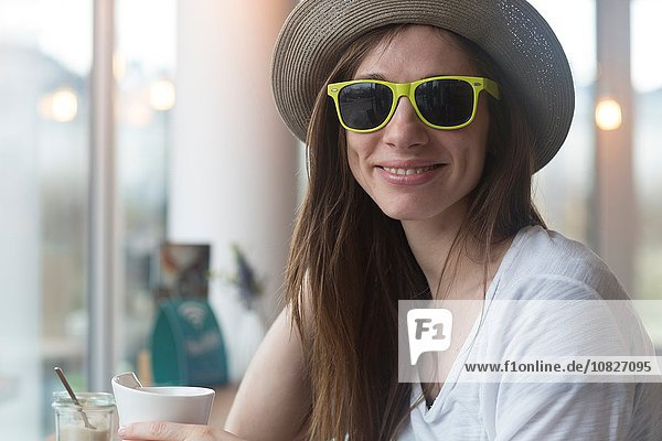 Junge Frau mit Strohhut und Sonnenbrille beim Kaffeetrinken im Café