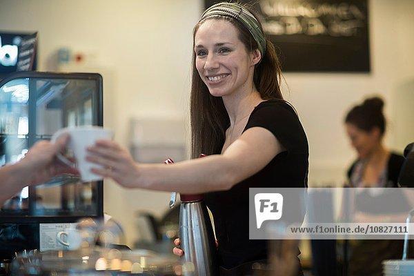 Junge Kellnerin überreicht Kaffee an Café-Kundin