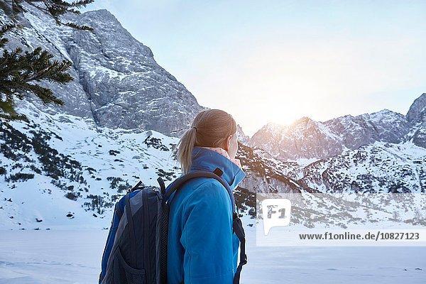 Junge Frau beim Wandern im Schnee und beim Beobachten der Sonne auf dem Berggipfel  Österreich