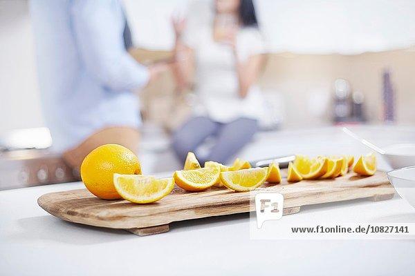 Quartered Orangen auf Küchentheke vor jungem Paar Quartered Orangen auf Küchentheke vor jungem Paar