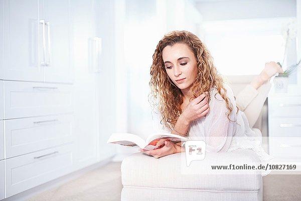 Junge Frau auf Ottomane beim Lesen eines Buches im Schlafzimmer