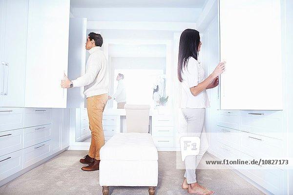 Junges Paar sucht in Schlafzimmerschränken