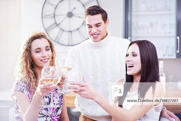 Three young adult friends making a white wine toast in kitchen