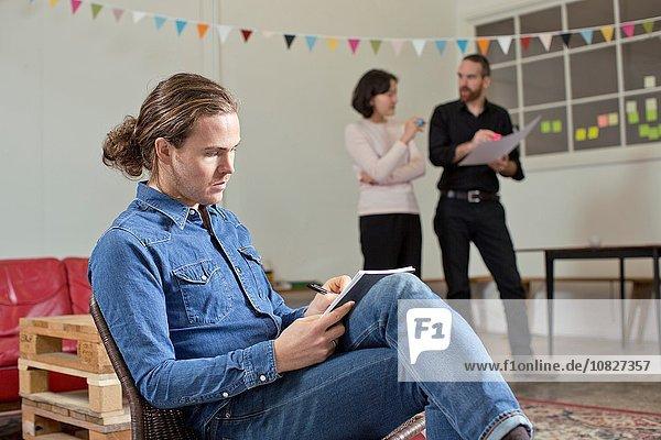 Mann schreibt Notizen  Kollegen im Hintergrund