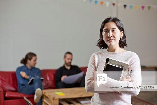 Frau mit Büchern  Kollegen im Hintergrund