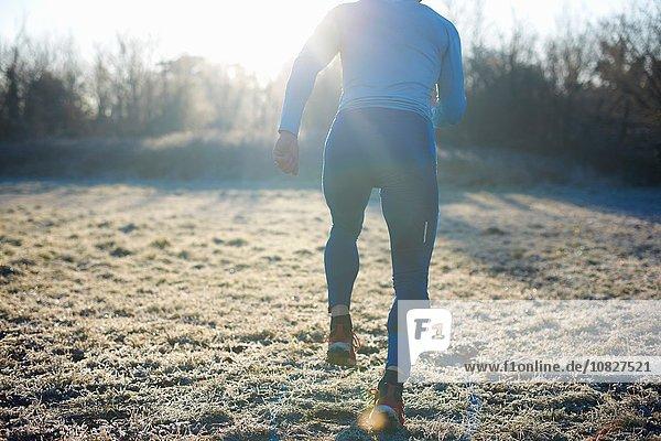Rear view of runner running on frosty grass