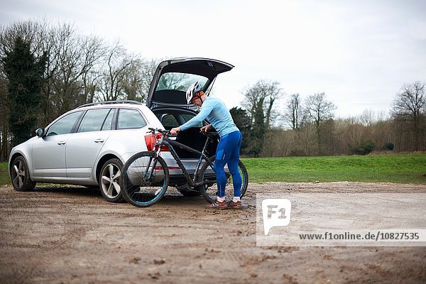 Cyclist wearing bicycle helmet unloading bicycle from car boot