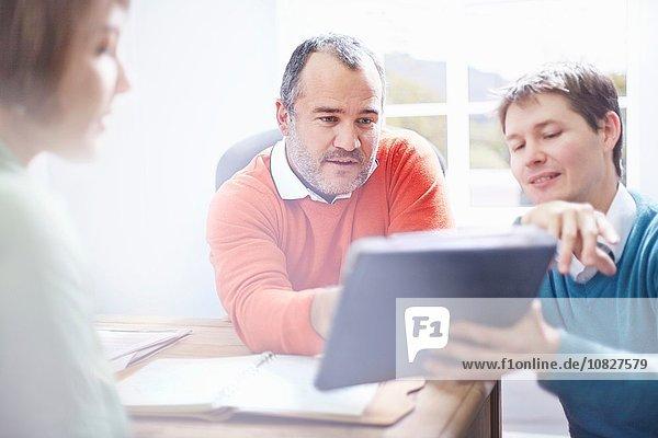 Mittlerer Erwachsener Mann im Büro zeigt Kollegen digitales Tablett